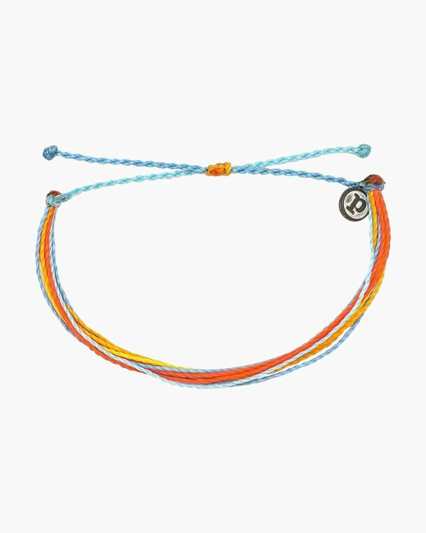 The Citrus Surfline bracelet from Pura Vida is decked out yellow, orange, and blue, and it can be adjusted for the perfect fit every time. Made from 100% waterproof cord and so much fun to wear and layer, it can follow you anywhere spring and summer take you - with a little boho flair thrown in to help you catch the waves!  Adjustable from 2-5 Inches in Diameter Wax-coated cord is 100% waterproof Pura Vida logo charm