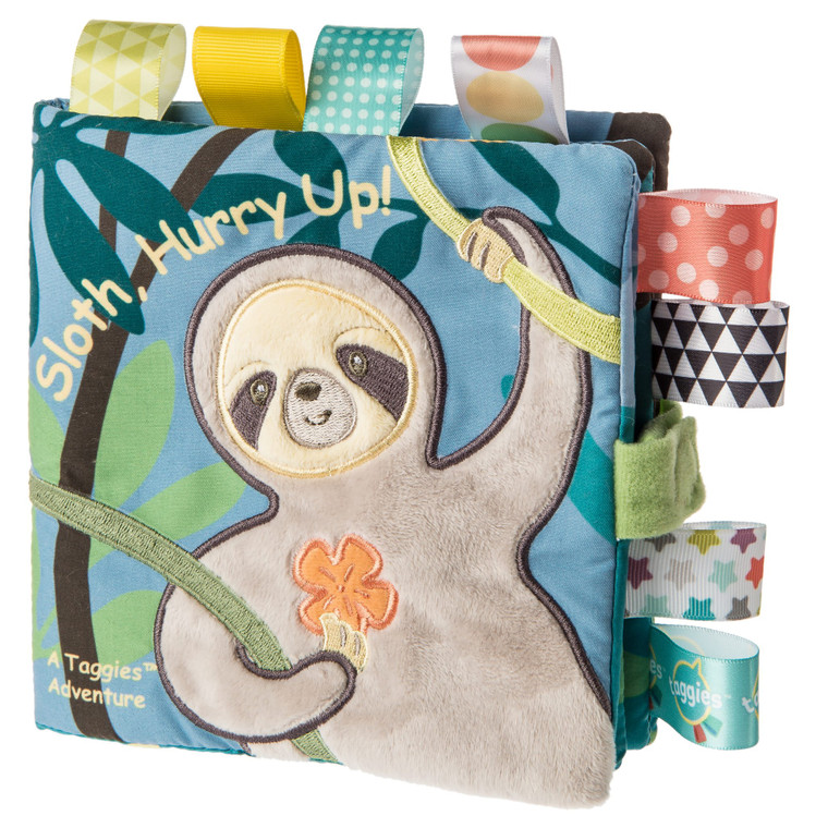 """Finalist for the 2019 Progressive Preschool Awards in the 'Best Infant Development' category  6×6″ Taggies was born over a decade ago when a mom noticed her child's fascination with satin tags. This idea blossomed into a world of treasured products.  Little ones are mesmerized by rubbing these soft, satin loops. Exploring Taggies textured tags can provide tactile stimulation that babies crave for development and have an amazing calming effect on little ones. Discover the secret too!  Taggies books are winning awards for their combination of stimulation (squeaker and crinkle paper inside) and soothing features (eight Taggies ribbons and textured fabric covers). Each book tells a short, sweet story in eight pages with Velcro® closure.  Begin each day with a long, slow hug. In the Baby market, sloths are hot! Molasses is our """"cute"""" version of a realistic sloth. Molasses Sloth is a truly gender neutral buddy. Naturally neutral color palette. Sloth is incredibly adorable, with a captivating face, and tags all over.  – 6×6″ Soft book featuring Taggies Molasses Sloth in a fun, calming, short bedtime story – 2-dimensional book with 3-dimensional details – On-trend greenery – Fabric applique cover – All-emboridered details – Lots of Taggies ribbons – 8 pages – Velcro® closure – Crinkle paper and squeaker inside – Coordinates with the Molasses Sloth collection – Machine wash, air dry"""