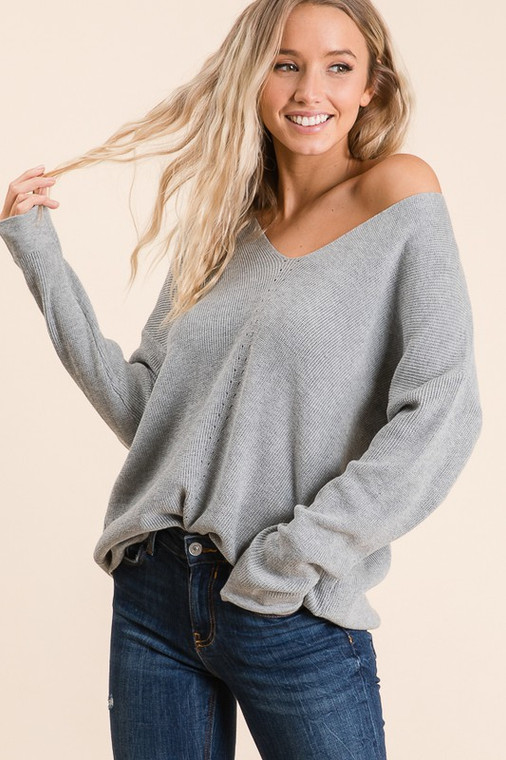 This is the year round sweater you need! Perfect grey color with adorable details down the front. The slight V allows for it to be worn traditionally on both shoulders or an easy tug to the side for an off the shoulder look.
