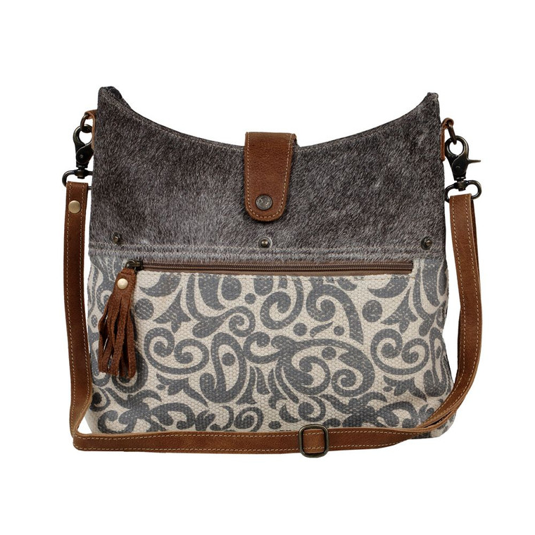 This upcycled canvas and leather bag is bound to become a favorite as because of its stylish look and perfect size. With its block print on rug fused with Hairon leather patch on the top and specs of leather tinges here and there with adjustable leather straps, it will lure all the souls.