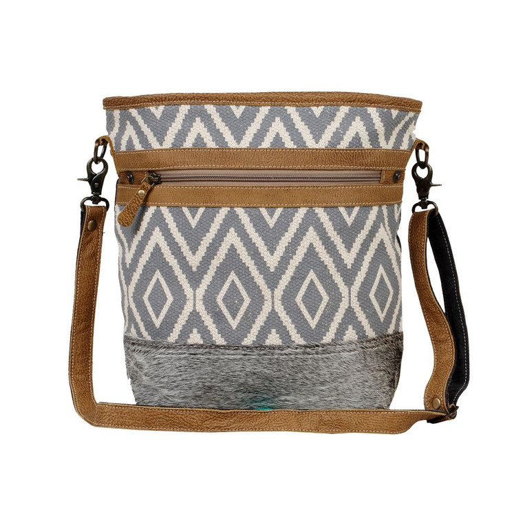 Another creation to brighten up your mood. Hairon leather bottom with adjustable leather straps and a front pocket teamed up with a fine-looking rug makes this bag enviable.This upcycled canvas and leather bag is bound to become a favorite as because of its stylish look and perfect size.