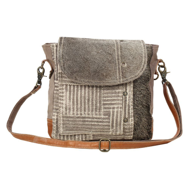This shoulder bag has chic fashion pattern and hairon flap. This bag features one front pocket and secures items inside. This upcycled canvas and leather bag is bound to become a favorite as because of its stylish look and perfect size.