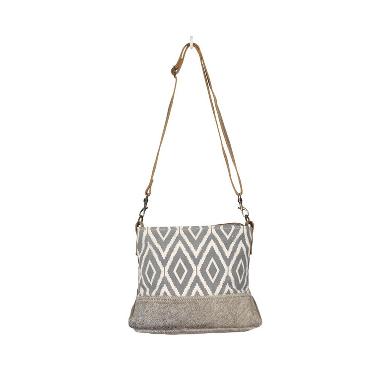 This shoulder bag has chic fashion cross design with hairon at the front bottom! Comes with zippered top closure to secures items inside. Made of upcycled canvas and leather, this bag is durable adn stylish.