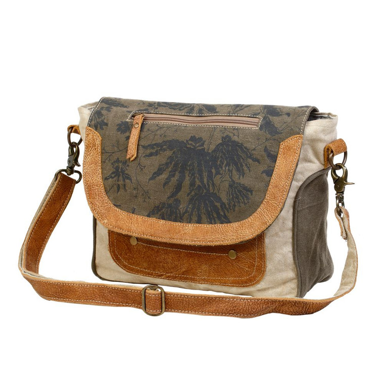 This is messenger bag has zipper pocket flap that looks fashion-forward. This bag features one front pocket. Made from upcycled canvas and leather, this bag is stylish, durable and environmentally friendly.