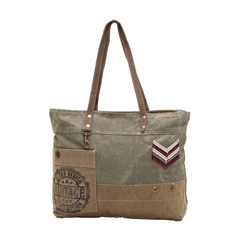 Military Badge Canvas Tote Bag comes with 11.5-inch over-the-shoulder straps allow for convenient carrying. Interior zippered pocket for security and convenience  Made from upcycled canvas and leather, this bag is stylish, durable and environmentally friendly.