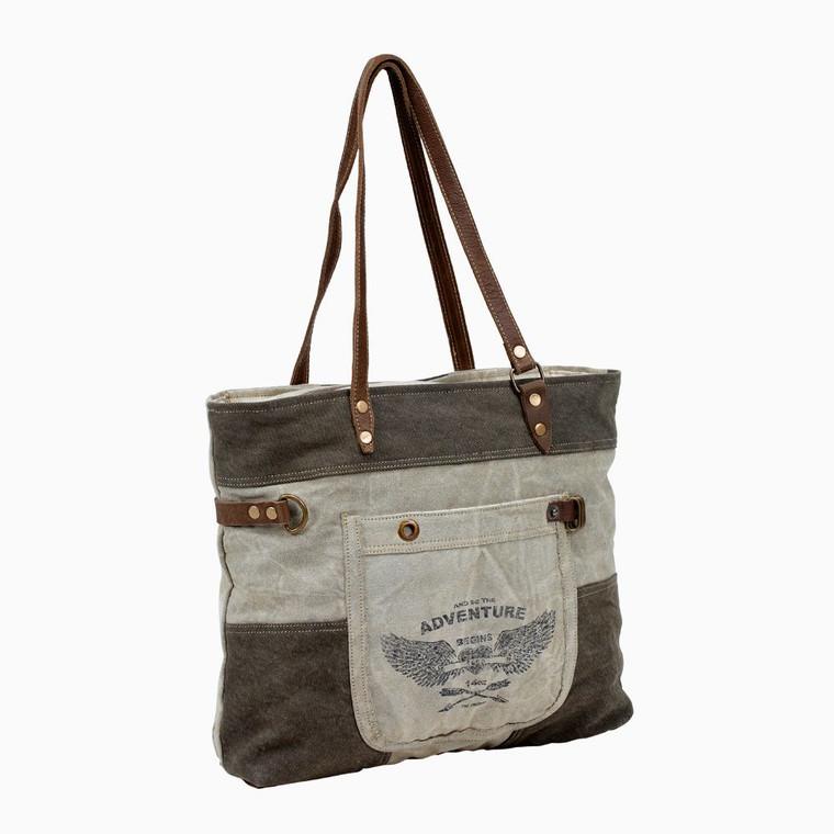 This tote bag is having a combination of denim, canvas and leather which fits comfortably over the shoulder. The adventure begins print on the pocket gives a nice look with genuine leather handles.  Made from upcycled canvas and leather, this bag is stylish, durable and environmentally friendly.