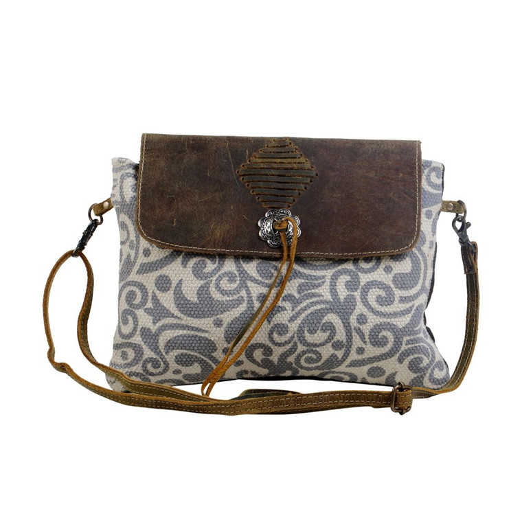 Made from an intricate rug design and comes with a leather flap to ensure safe storage. This crossbody bag also has a zipper at the back to accommodate small essentials.  Made of upcycled canvas and leather.
