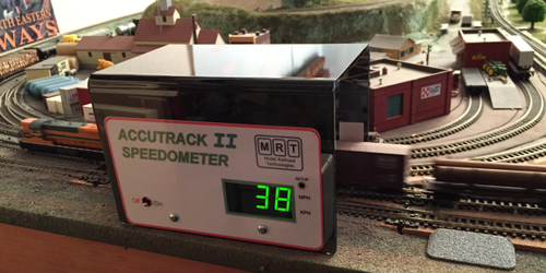 "Accutrak II Speedometer by MRT Introducing the Accutrack II Model Train Speedometer  Note:  This is a portable, stand-alone speed detection device.  It works with DC or DCC layouts.  It works with any DCC system since they are not connected in any way.  Model Railroad Technologies is please to announce the development of the Accutrack II Speedometer for measuring scale speeds of model railroad locomotives and trains. The Accutrack II includes several features not present in the original Accutrack Speedometer.  We have listened to customer and dealer input and have incorporated the most desired new features and functions. Although several small changes have been made in the nearly 10 years that the Accutrack has been on the market, no major redesign has been done up until now.  These new features include: Clearance for HO scale AutoMax cars and double stacks with high box containers. Several modelers running modern equipment could not run their AutoMax equipped trains through the existing model. With the Accutrack II they can! (see photo). The addition of OO (4mm) and N Gauge (9mm) to the existing HO (1:87) and N scale (1:160) settings. The addition of Kilometers per hour (KPH) as a unit of measure for all included scales.  Scale selection includes the ability to select each of the included scales with measurement displayed in either miles per hour (MPH) or kilometers per hour (KPH). Display resolution is:  •	.1 mph/kph up to 10 •	1 mph/kph for 10 and above Adjustable automatic Power Down time. Originally limited to powering down after 5 minutes of no train activity, this time period is now adjustable from 1 minute to 30 minutes. The power down feature can also be disabled completely, if desired, but re-enabled as desired. We believer that these new features, coupled with the simple, no installation setup of the original Accutrack, will add to the enjoyment of serious model railroaders, whatever their interest.  Model Railroad Technologies Accutrack Speedometer   The MRT Accutrak Speedometer is a free standing, battery operated scale speedometer HO and N scales.   Its design is based upon infrared beams which create a ""trap"" zone through which the train travels.   Speed is then calculated based upon the scale elected from the front panel and the time determined by the internal microcontroller.   The result is displayed on the front panel. The Accutrak Speedometer comes with scale speed factors for N and HO scales already programmed in. Accutrak II Features: •	Ideal for speed matching DCC locomotives.  •	Operates on 2 AAA batteries (included). •	No Installation required – sits over track. •	Infrared beam based – no room lights required. •	Clearance for HO scale AutoMax cars and double stacks with high box containers. •	Scale Selectable from front panel – N (1:148 and 1:160) or OO/HO (1:76.4 and 1:87) •	Display increments: o	.1 mph up to 10 mph or kph o	1 mph above 10 mph or kph •	Cycle starts when train enters either end. •	Cycle ends and speed is displayed when train trips second beam. •	Speed is displayed for 5 seconds and then unit goes into power saving mode. •	Adjustable auto shut off between 1 to 30 minutes of no trains.   Size: 5.50 x 3.8 x 3.3 Inches (140 x 97 x 84 m"