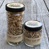 Solvang Spice merchant spice jar options in a 1 cup glass jar and 1/2 cup glass jar sitting side by side on a rustic wood table