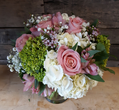 Hydrangea, roses and hypericum berries are accented with spring garden accents to create a soft and elegant design that will bring a bit of springtime into any home or office