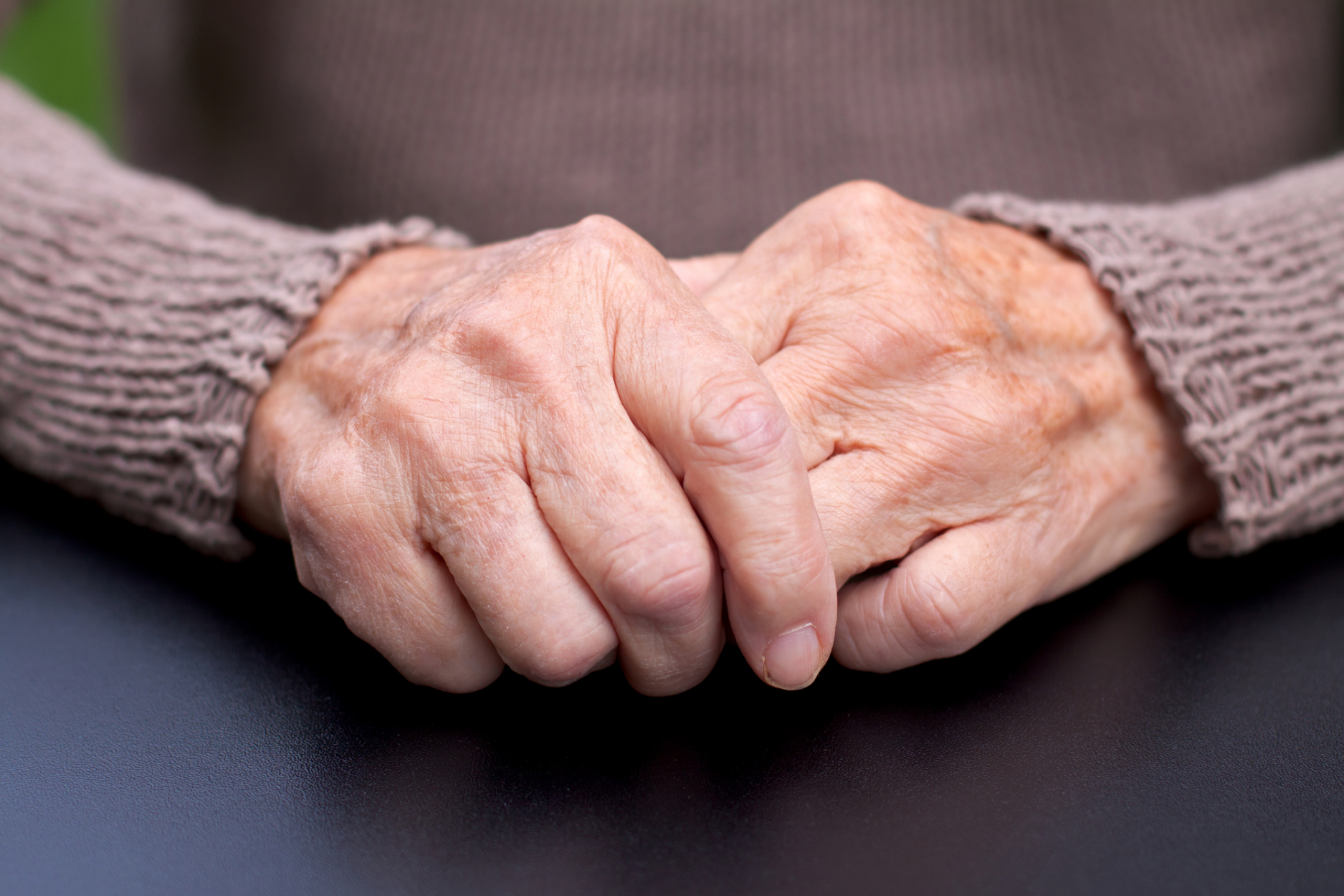 Clasped, elderly hands that look like they may have joint pain.