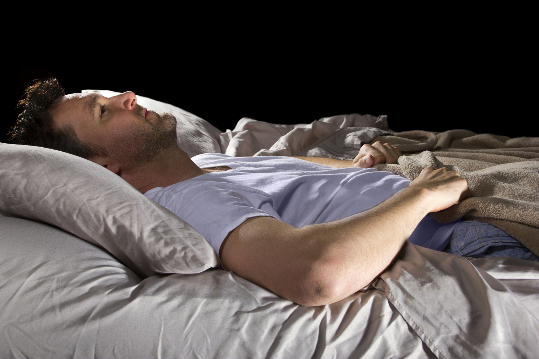 Man lying in bed staring at the ceiling.
