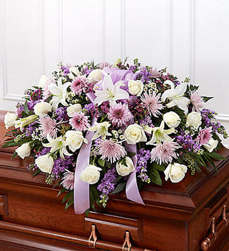 Lavender Half Casket Cover When we lose someone dear to us, we want to respond with a fitting gesture of respect and admiration. Our half casket cover, crafted with care and artistry by our expert florists with lavender cremones, mums, white roses, and accented with a lavender satin ribbon, is an unforgettable way to commemorate a lifetime of loving devotion.