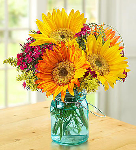 Warm Sunset Bouquet Deliver the most beautiful part of the day right to their door! Our bright orange and yellow sunflowers are grown and picked at their peak on select floral farms and gathered together to deliver a smile to someone special.