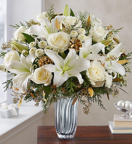 EXCLUSIVE Share winter's undeniable radiance with one unforgettable gift. Our luxurious new arrangement flaunts an abundance of all-white blooms, evergreens and glistening gold accents. It's all artistically designed inside our exclusive Silver Radiance Vase with soft, silvery cascades and an elegant fluted shape to take this sparkling seasonal bouquet to a whole new level of brilliance.
