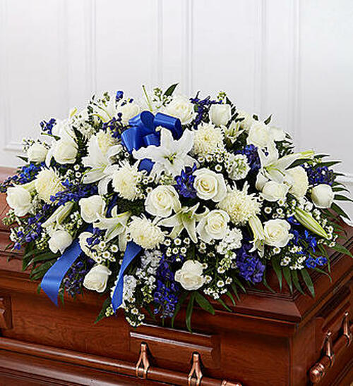 Blue & White Mixed Half Casket Cover Honor a life so beautifully lived with a proud display of blue and white blooms. Our half casket cover, crafted with care and artistry by our expert florists with blue delphinium, white roses, and accented with a blue satin ribbon, is an unforgettable way to commemorate a lifetime of loving devotion.