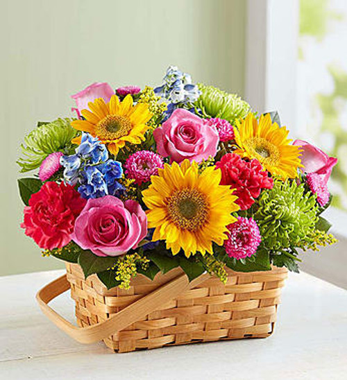 "Sunny Garden Basket There's so much about a garden to inspire""vibrant colors, sweetly scented blooms... and that's why we've captured it all in one charming basket! Filled with a beautiful mix of roses, sunflowers, daisies, and more, our hand-designed arrangement will inspire them to smile brighter, laugh longer... and delight in the moment forever."