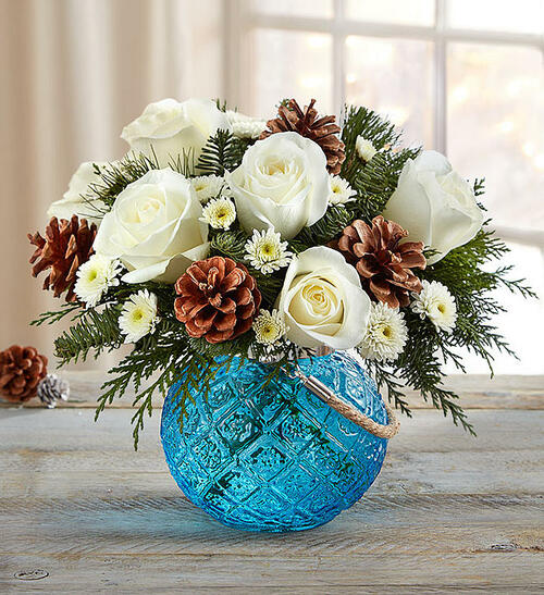 EXCLUSIVE Warm up their winter with our standout bouquet that blends rustic charm and global chic. Bright white blooms look just like freshly fallen snow against a mix of evergreens and pinecones. And for a truly unexpected - and eclectic - surprise, we've paired it with our exclusive new bubble vase. Inspired by the rich blue water of the Mediterranean Sea, it features an antique pressed glass design and rustic rope handle. An added tea light candle transforms this piece into a unique candle holder, bringing beauty and vibrancy into any home.