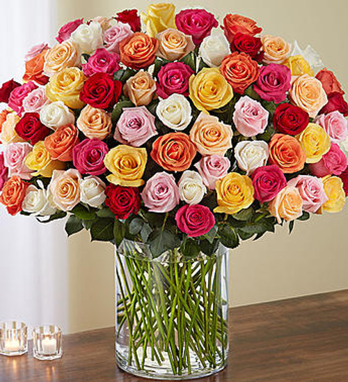 Wow someone like never before with 100 stunning long stem roses in a rainbow of colors! Our spectacular arrangement is artistically designed by our expert floral artisans with an abundant array of blooms in every color, gathered with lush greenery inside a classic cylinder vase. Standing over 2 feet tall, this brilliant surprise is personally hand-delivered to help your express how you feel in the biggest and best way possible.