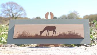 Wood engraving on Maple, Deer grazing in field