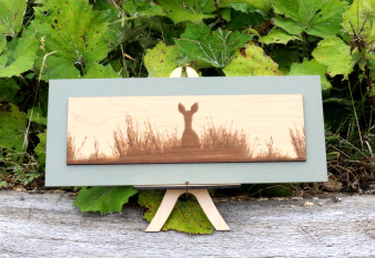 Wood engraving on Maple, Deer peering over bank