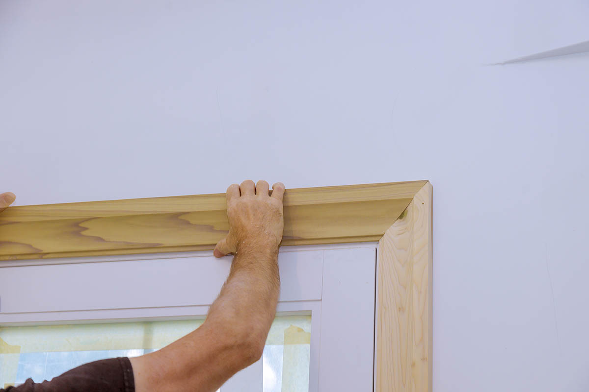 carpenter-installing-moldings-doors-nailing-framing-trim.jpg