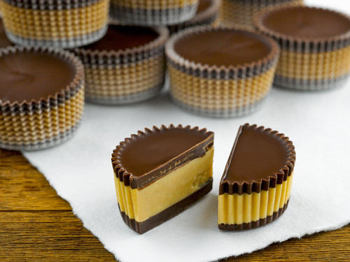 Dark peanut butter chocolates piled on top of white fabric with one chocolate cut in half View Product Image