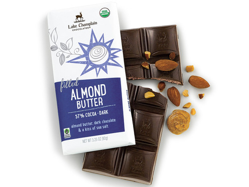 Almond butter dark chocolate bar in a wrapper and outside the wrapper with pieces of almonds and a spoonful of almond butter View Product Image