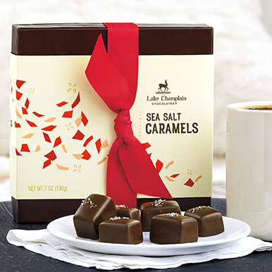Milk chocolate sea salt caramels on a plate with a gift box behind it