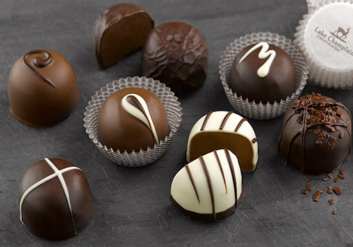 assorted chocolate truffles displayed on a slate plate