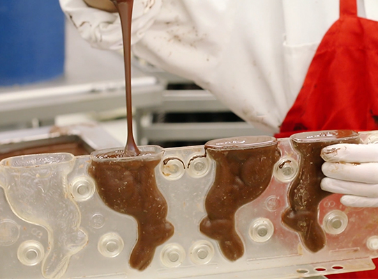 person pouring chocolate into a bunny mold