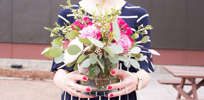 woman holding a pink flower arrangement