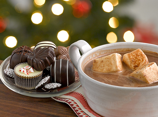 holiday chocolates and hot chocolate in front of the tree