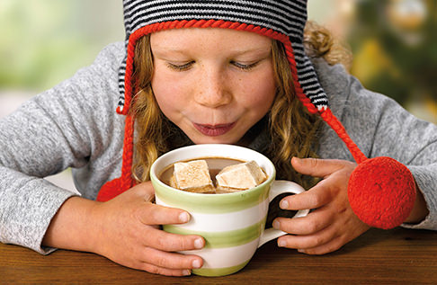 Girl getting ready to drink a cup of hot chocolate with marshmallows