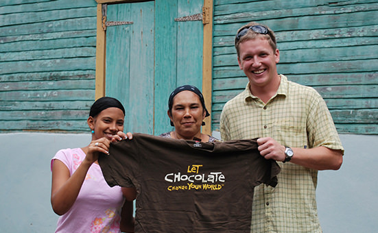 Eric with cocoa farmers holding a chocolate tshirt