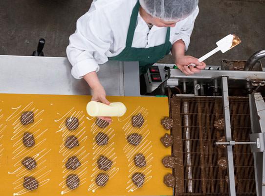 hand decorating macadamia caramel clusters