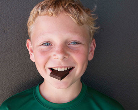 boy eating square of chocolate