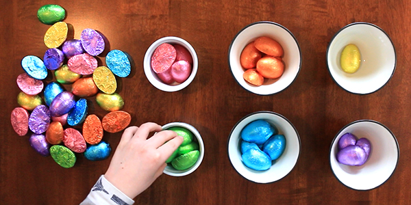 sorting foil-wrapped chocolate eggs by color