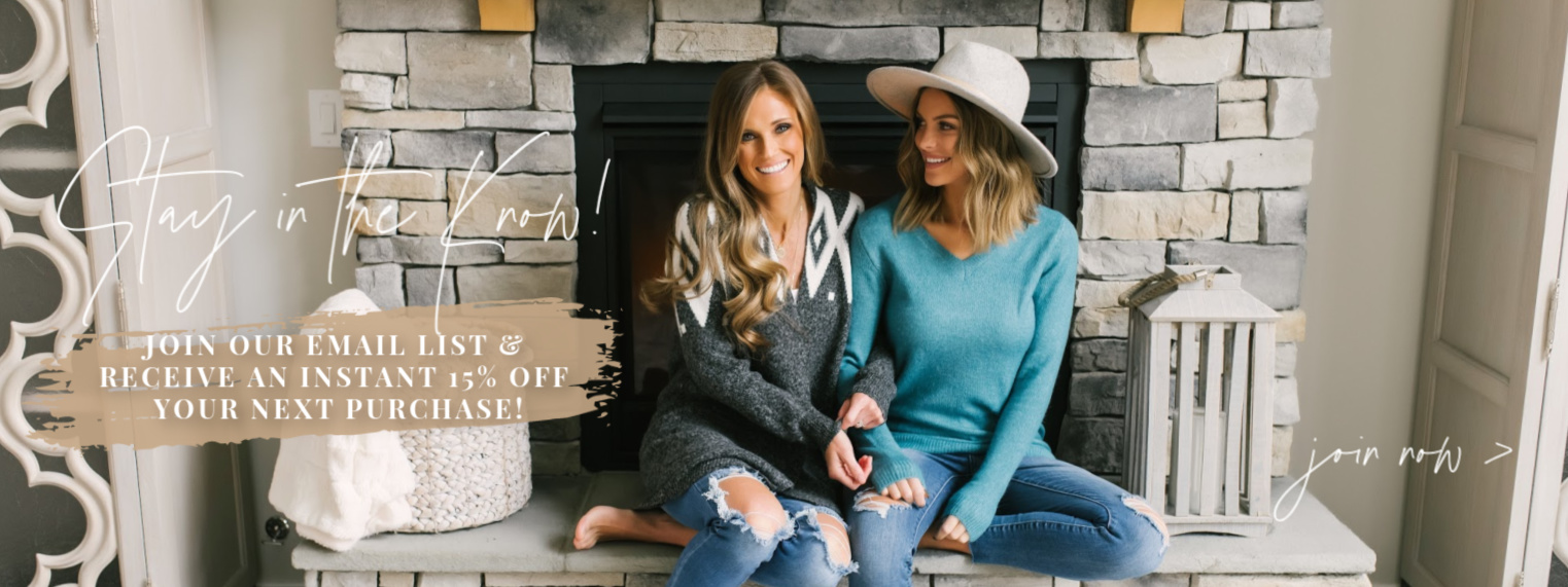 two girls in sweaters by fireplace