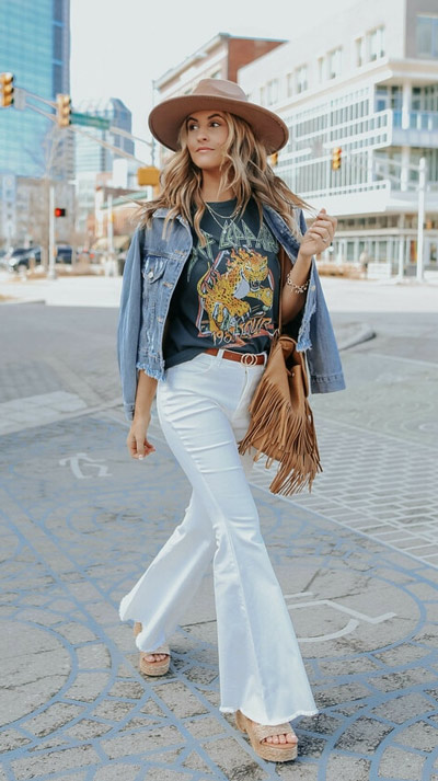 woman walking down the street in black def leppard graphic tee, white flair pants, and jean jacket