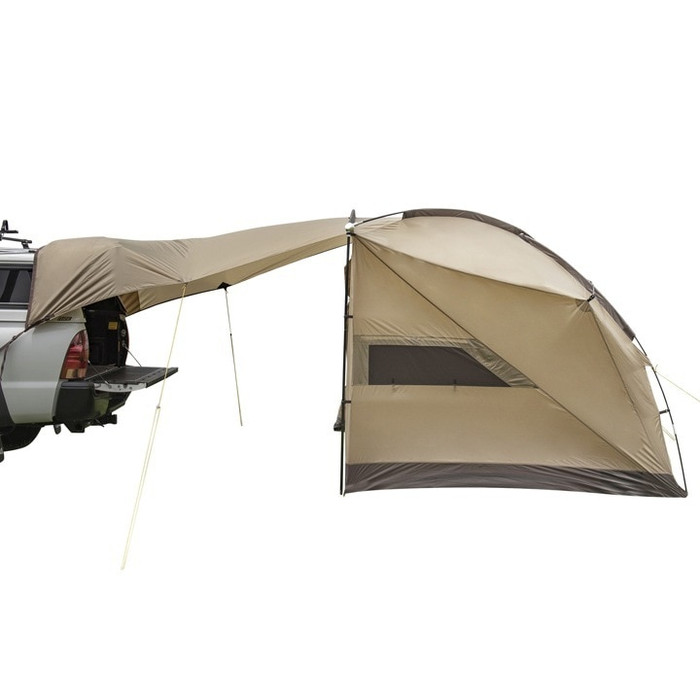 Slumberjack Slumber Shack 4 Person Tent, tan. Tent is shown completely assembled with awning feature attached to the back of a Toyota pickup with a camper shell.