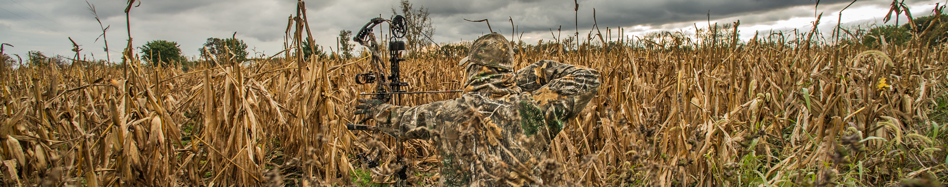 Man in camo hunting in a cornfield
