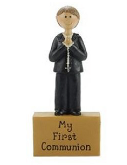 "First Communion boy holding a rosary standing atop a block featuring the words ""My First Communion"". Measures 4.2"" x 2"". A Blossom Bucket collectible."