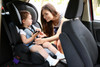 Buckle Booster™ in use buckling in a child sitting in a car seat.