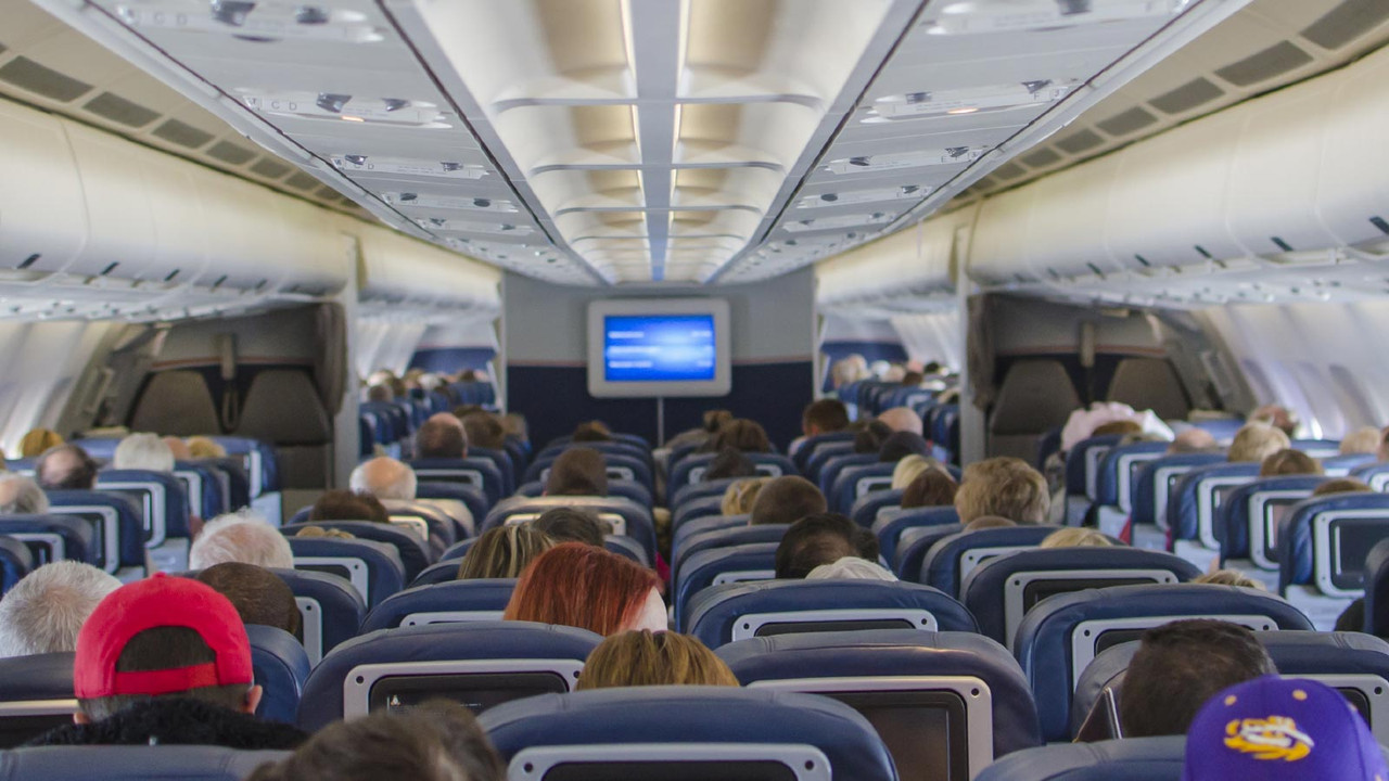 The inside of a plane's cabin is shown from the back.