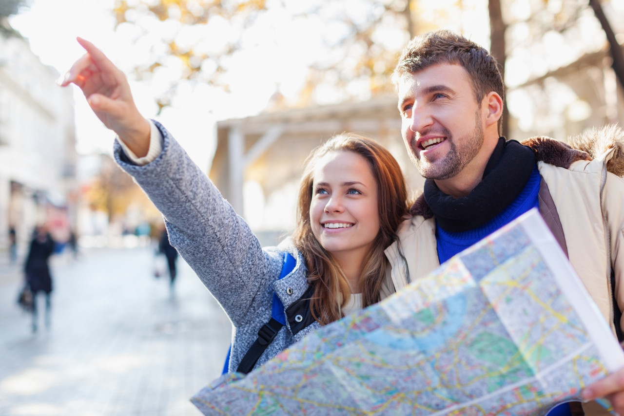 A male and female couple looks at something in the distance while holding a map during their travels