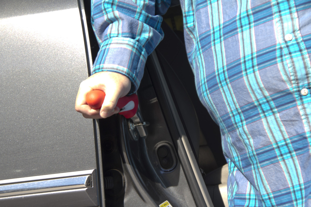 A man leaning against the Auto Assist Safety Tool to get out of his car.