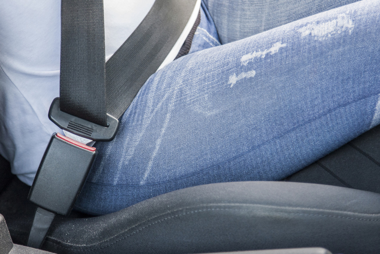 The side of a woman's hip sitting in a car as she is buckled into the car with an extender.
