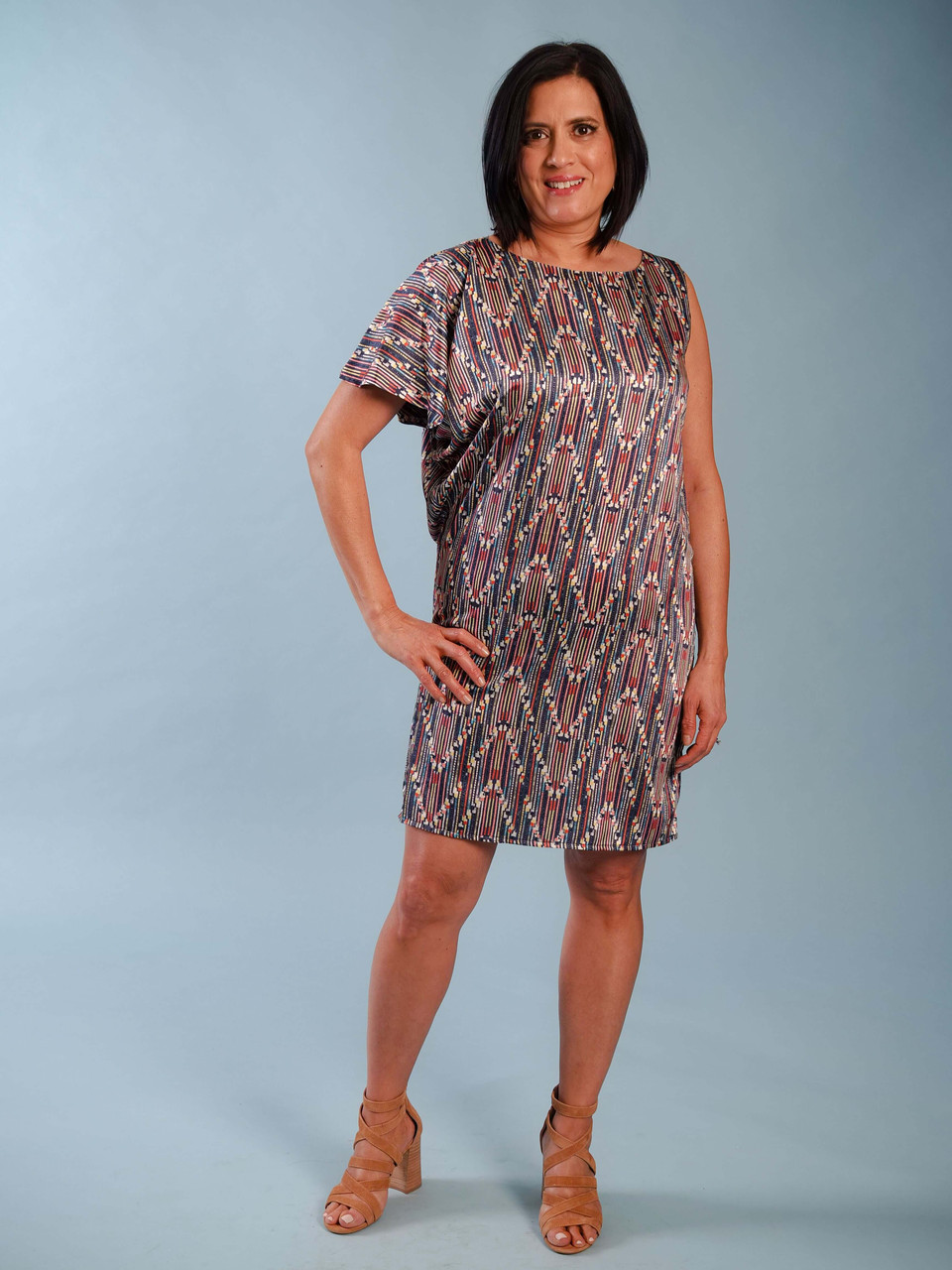Colorful modern lightweight dress with asymmetric sleeves, Model is wearing a small.