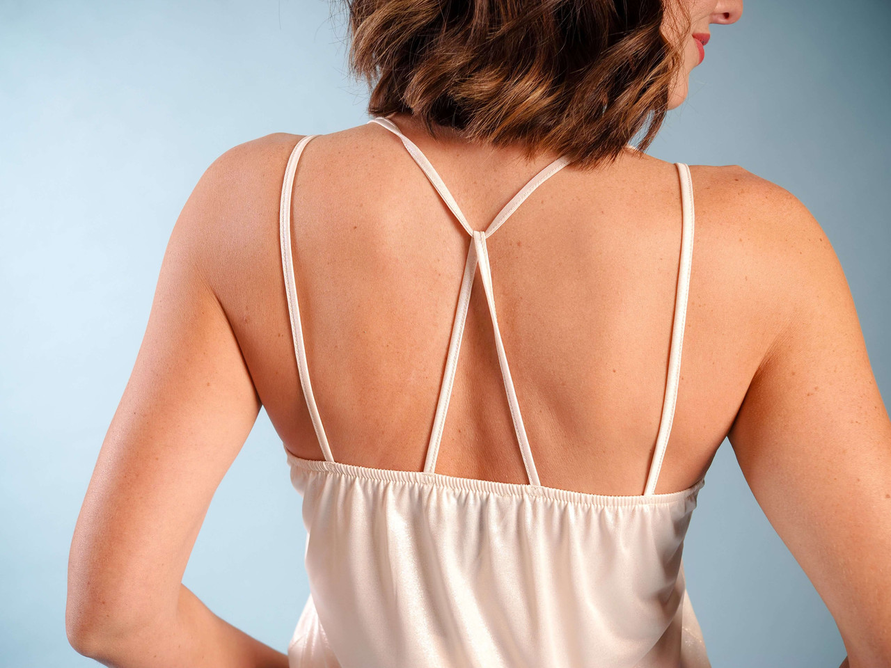 Iridescent soft beige v-neck modern camisole, Back crisscross straps, Model is wearing a small/medium.